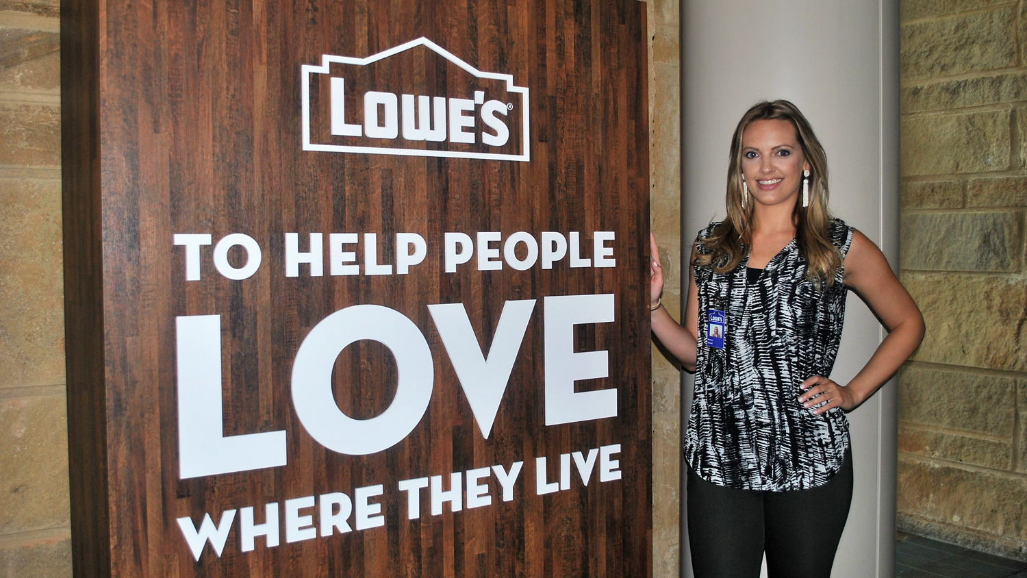 Female intern standing in front of Lowe's Companies sign.