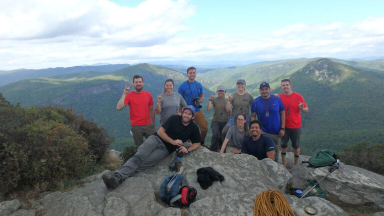 10 smiling people pose for a group photo on top of a mountain