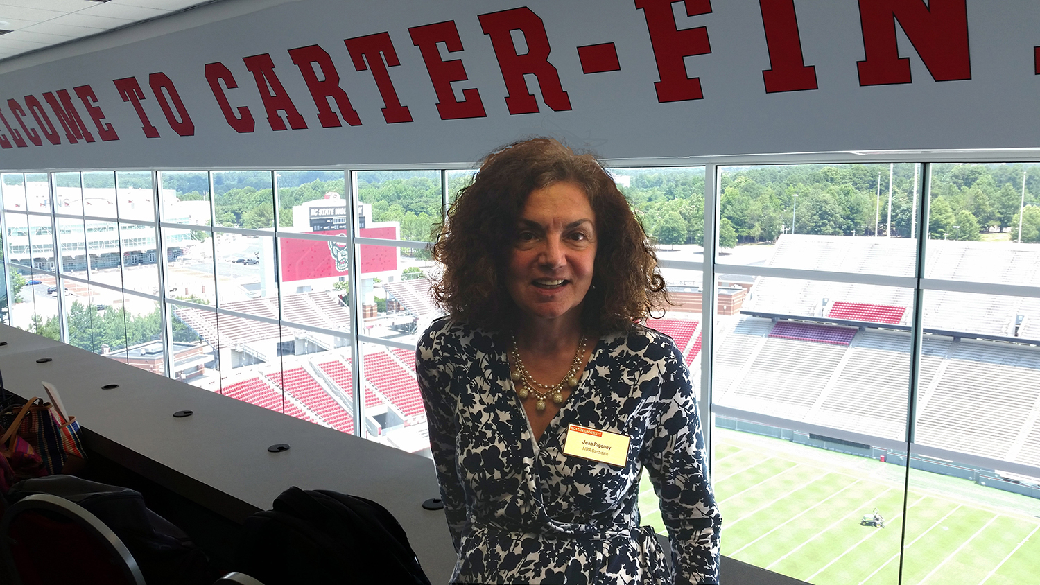 Jean Bigoney at one of the Jenkins Professional Online MBA Program Raleigh Residency events. Jean is pictured in the suites at Carter Finley Stadium overlooking the field.
